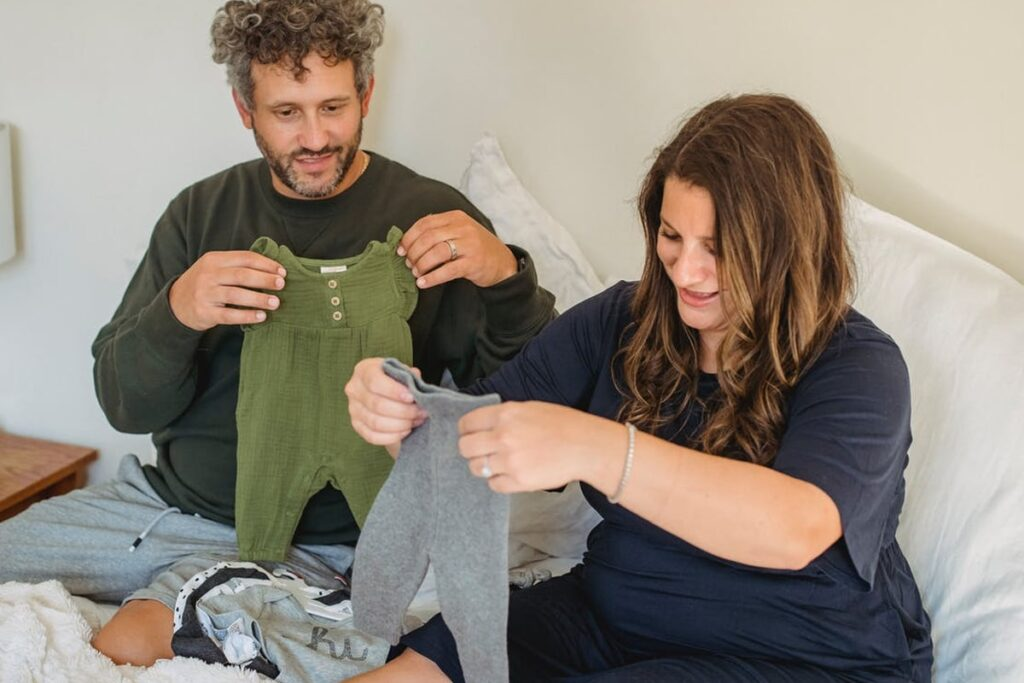 Couple selecting clothes for baby