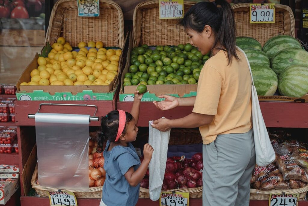 Mother and daughter buying  bulk of fruits