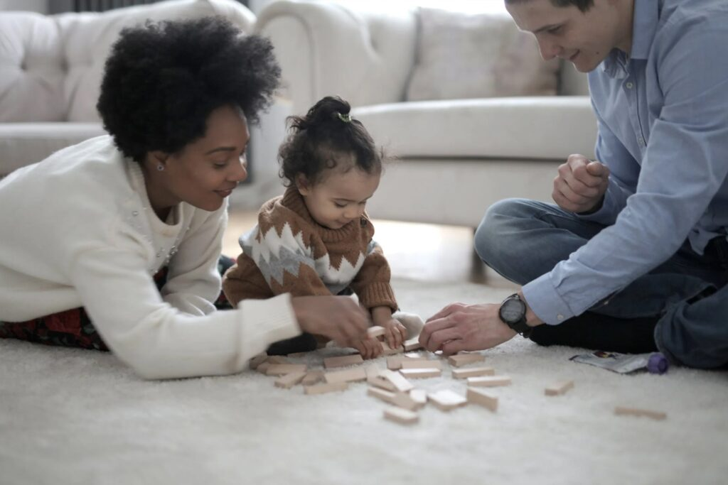 Mother and father playing wooden blocks with their daughter