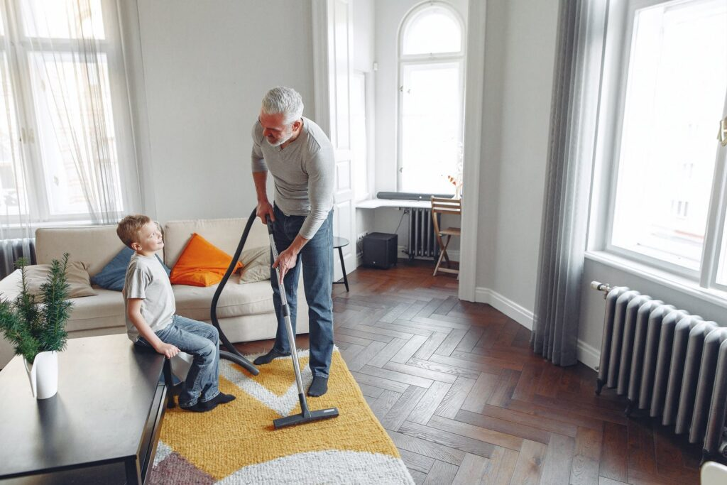 Dad showing his son happily cleaning the carpet
